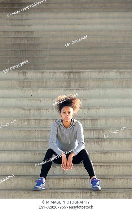 Portrait of an attractive young sports woman sitting alone on steps