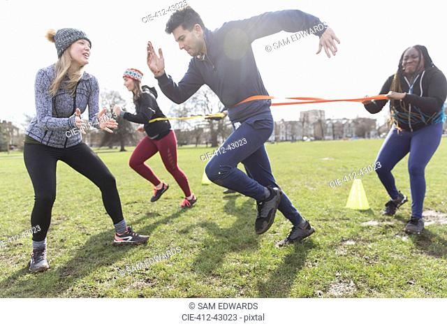 People exercising, doing team building exercise in sunny park