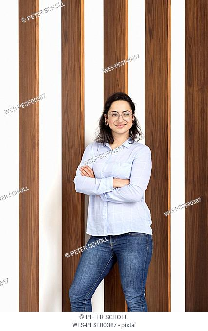 Smiling young woman in front of wooden wall