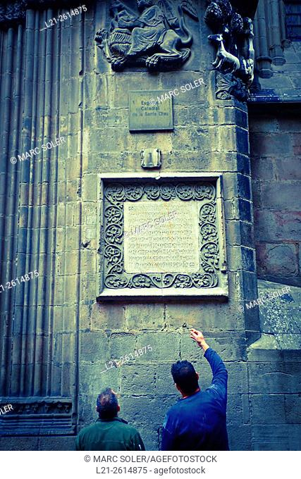 A man pointing a medieval inscription on a wall of Barcelona Cathedral. Barcelona, Catalonia, Spain