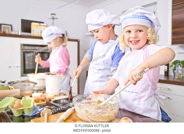 Germany, Girls and boy preparing dough and baking cup cake in kitchen