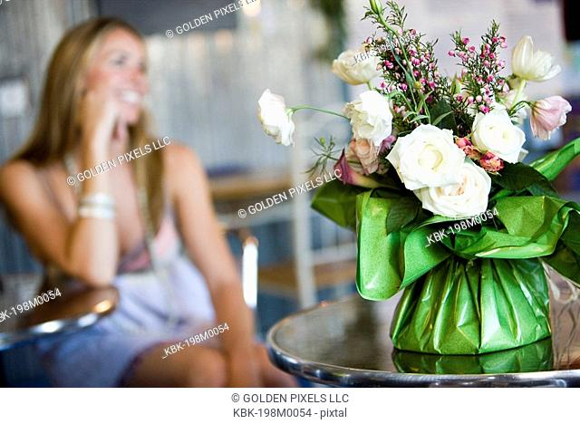 Flower arrangement in cafi with young woman in background