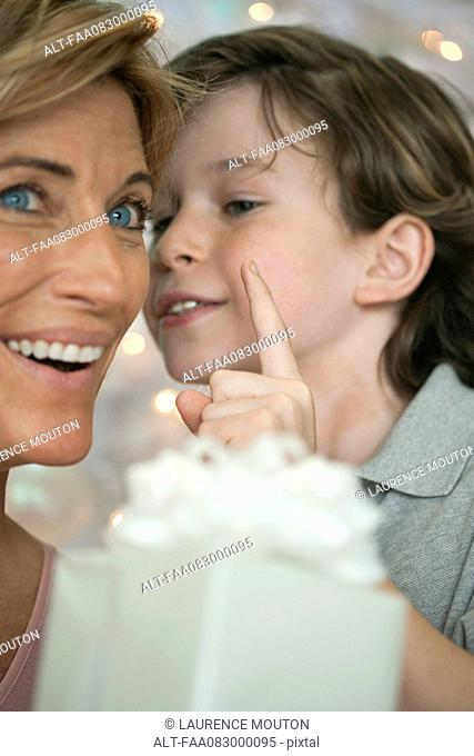 Mother holding gift, son whispering into ear