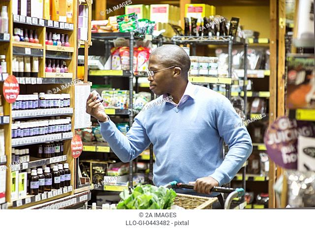 Man looking at product while shopping in health store in Johannesburg, South Africa