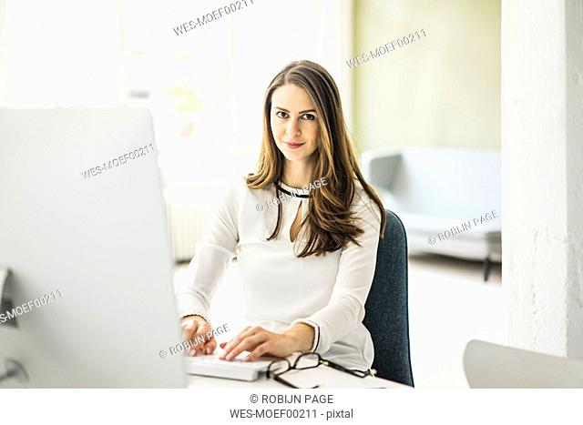 Portrait of confident businesswoman working at desk in office