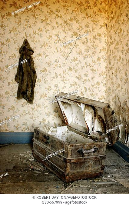A coat hangs on the wall above an open trunk in a Bodie residence, CA, USA