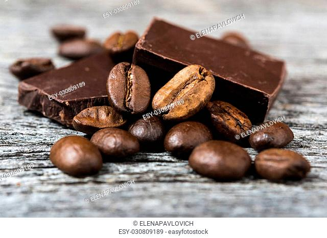 close up of coffee beans and chocolate on gray wooden background