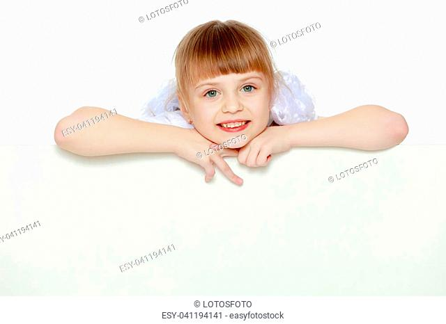 Funny little blonde girl with pigtails and white bows on her head in a white T-shirt and shorts.She hid behind the white banner ad and peeks out because of him
