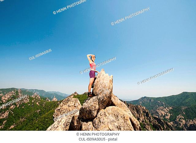 Female hiker looking out from rock formation on way to Daecheongbong peak, Seoraksan National Park in South Korea