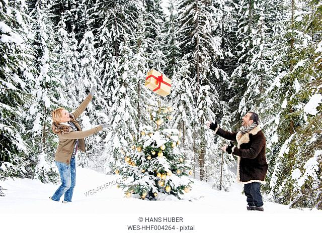 Austria, Salzburg County, Couple playing with christmas gift in snow, smiling