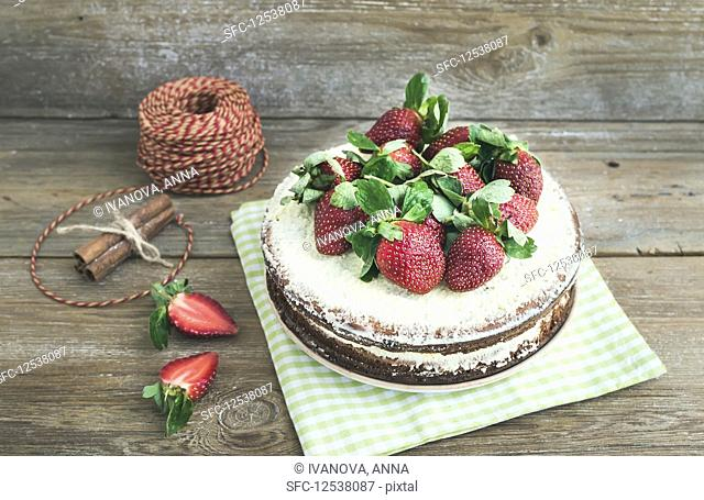 Rustic spicy ginger cake with cream-cheese filling and fresh strawberries
