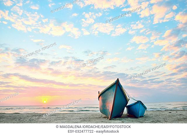 Blue boats on beach at sunrise