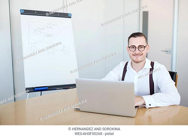 Portrait of confident businessman using laptop in conference room in office