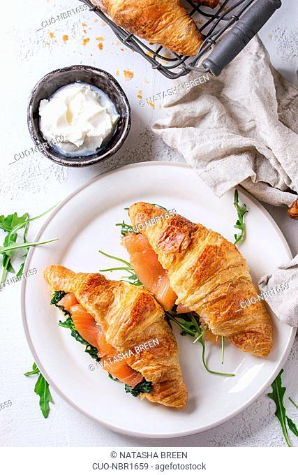 Croissant with smoked salted salmon, spinach and arugula served on white plate with bowl of cream cheese and coffee maker over white texture concrete background