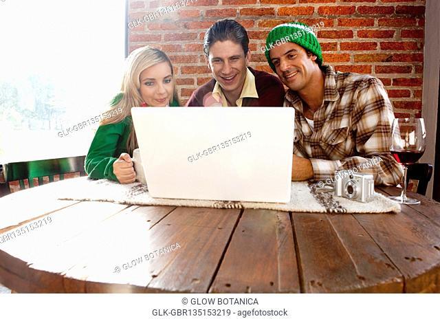 Friends using a laptop in a restaurant