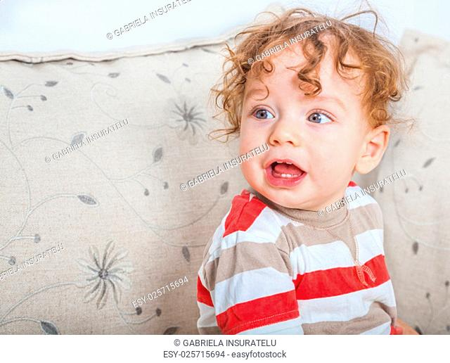 11 months old baby boy portrait playing on the sofa at home