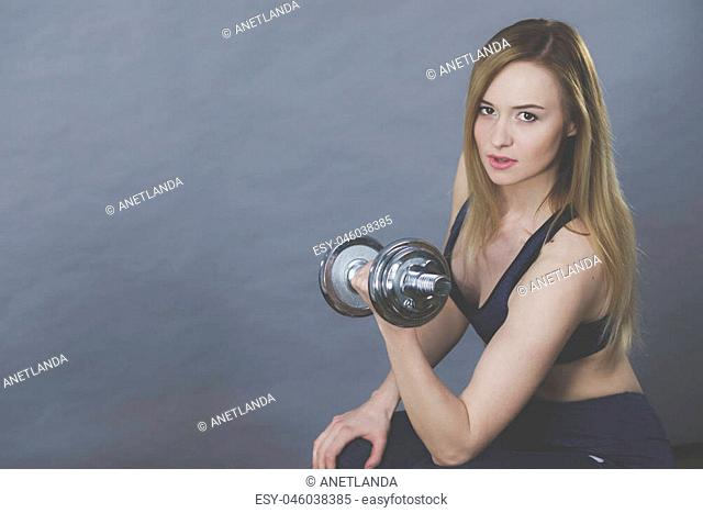 Strong woman lifting dumbbells weights. Fit girl attractive blonde model exercising gaining building muscles. Fitness and bodybuilding, on grey