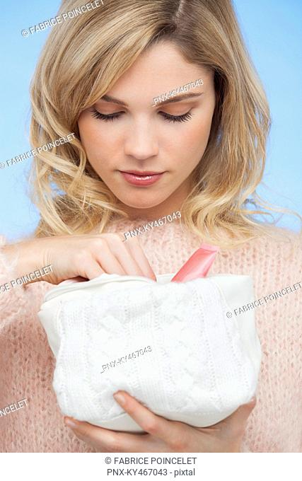 Portrait of a beautiful woman holding a makeup bag