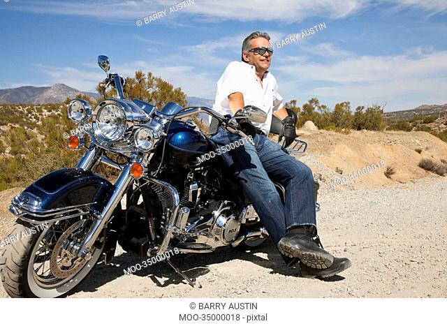 Senior man leaning on motorcycle on desert road