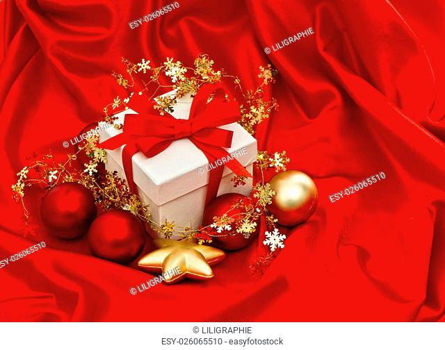 White gift box with christmas decoration over silk background. Red gold baubles stars