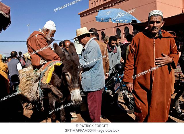 A MAN ON A DONKEY AT THE ENTRANCE TO THE BERBER MARKET OF TAHANAOUTE, AL HAOUZ, MOROCCO