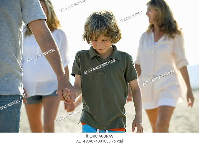 Boy walking on beach with family, holding father's hand