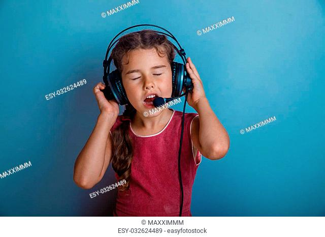 Teen girl singing in a microphone and listening to music with headphones on a blue background photo studio