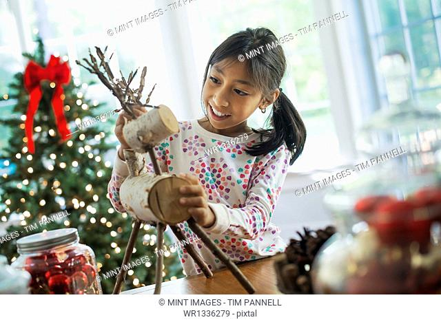 A young girl assembling a twig figure of a reindeer, making Christmas decorations