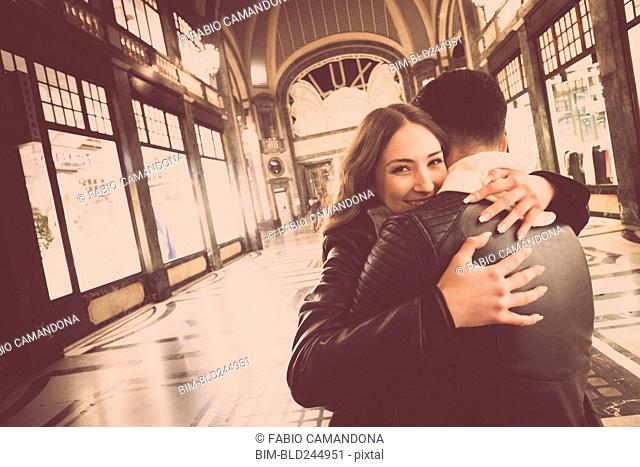 Smiling Caucasian couple hugging in lobby