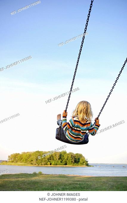 Rear view of child on rope swing