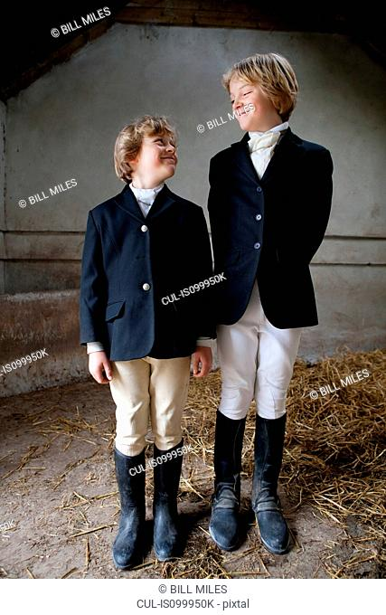 Boys wearing horse riding clothes in stable