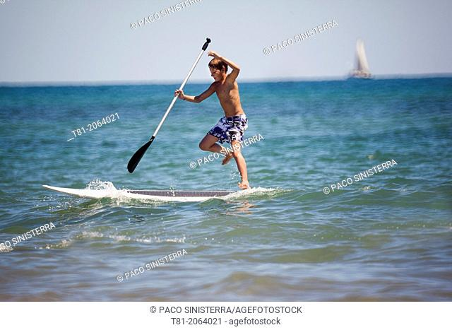 Boy with surfboard paddling about in the Mediterranean Sea, Benicassim, Castellon province, Comunidad Valenciana, Spain