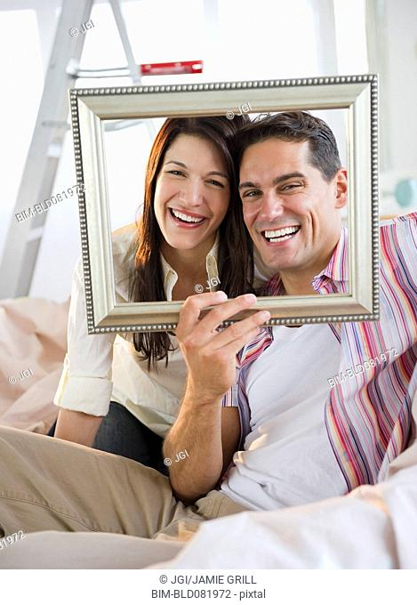 Smiling couple looking through empty frame