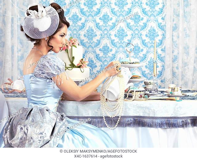 Beautiful asian lady in a luxurious blue dress sitting at a table and pouring tea ina cup  Tea party hostess