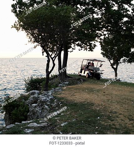 People in a golf cart parked at the edge of the sea