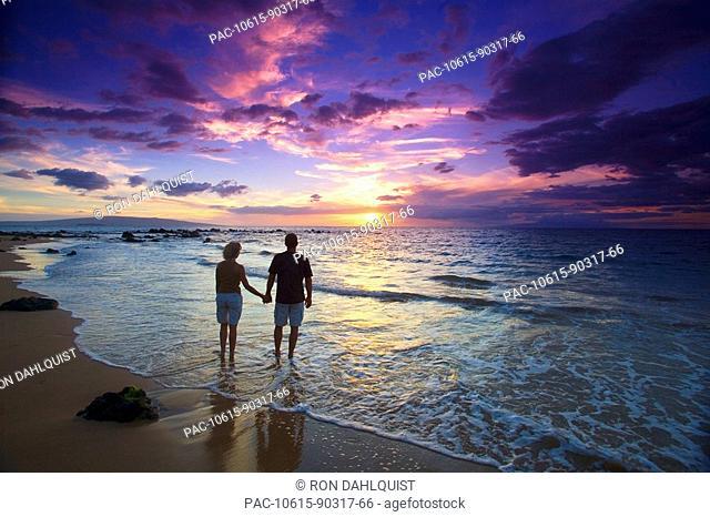 Hawaii, Maui, Wailea, Mokapu Beach, Silhouetted couple watching sunset