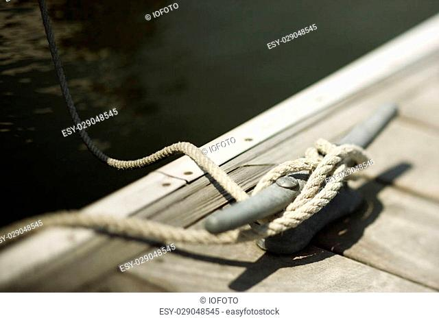 Rope tied to cleat on boat dock