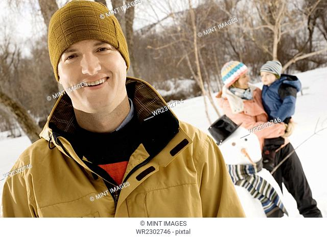 A man smiling in the foreground, and a woman holding a child beside a snowman