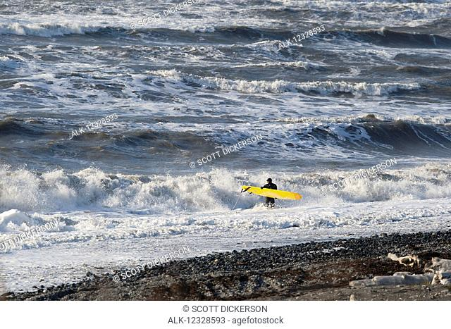 Surfer with his board entering the surf with crashing waves in the background, Southeast Alaska; Yakutat, Alaska, United States of America