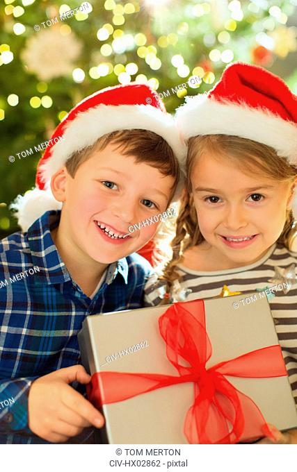 Portrait smiling brother and sister in Santa hats holding Christmas gift