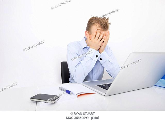 Tired businessman with hands on face sitting at desk by laptop