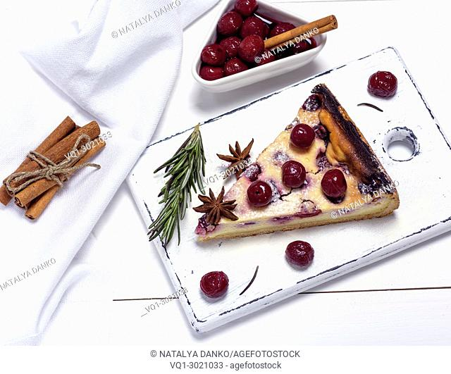 piece of cottage cheese pie and canned cherries on a white wooden board, top view