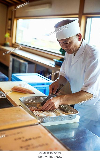 Chef working at a counter at a Japanese sushi restaurant, preparing fish in metal tray