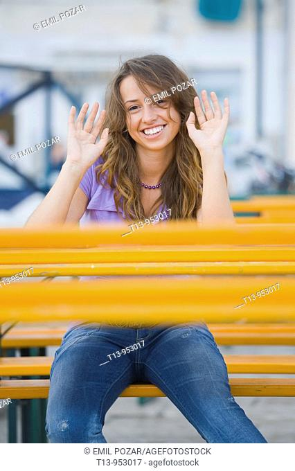 Young woman sitting behind Orange table acting 'hands up'