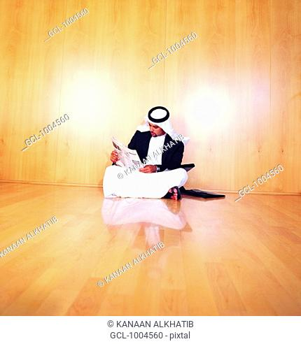 Saudi Arabian businessman reading newspaper