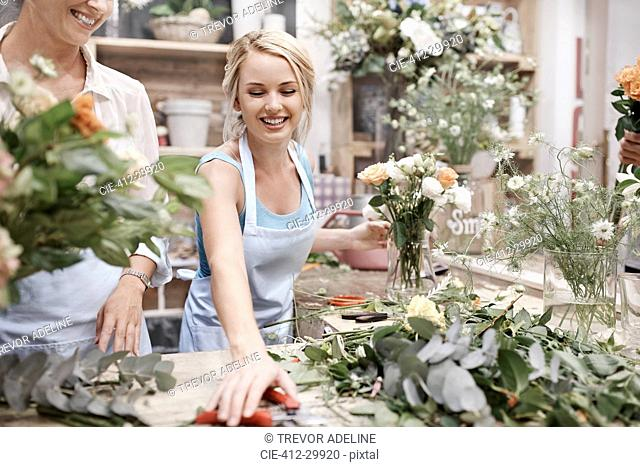 Smiling florist arranging bouquet in flower shop