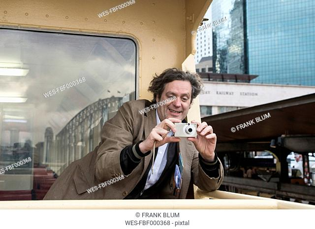 Australia, New South Wales, Sydney, man on ferry taking picture of harbour bridge