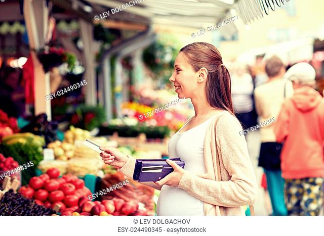 sale, shopping, pregnancy and people concept - happy pregnant woman with wallet and credit card buying food at street market