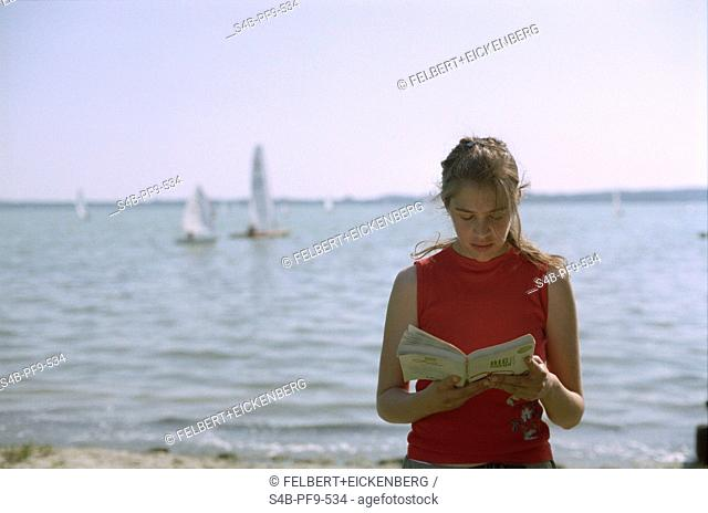 Young woman reading a novel in front of a lake