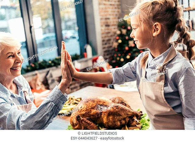 grandmother and granddaughter giving high five on thanksgiving after successful turkey cooking